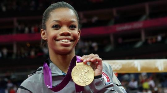 Olympic gymnastic Gabby Douglas holding her gold medal.