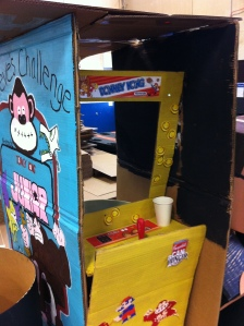 A mock arcade cabinet for Donkey Kong  made with cardboard and a metal barrel.