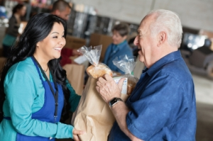 Photo of a young woman handing a bag of groceries to an older man.