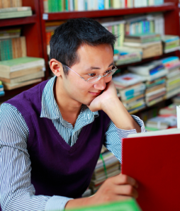 Photo of a young man reading a book.