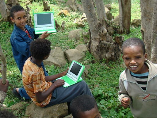 Three kids in Ethiopia using laptops.