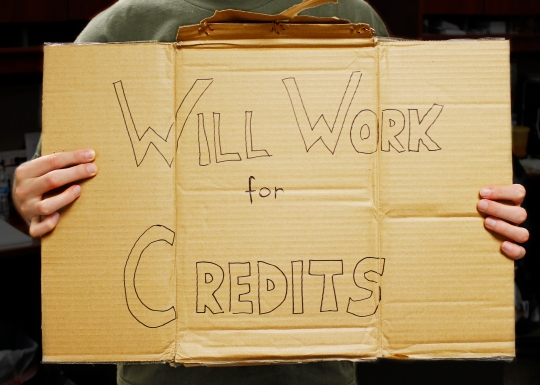 "Hands holding a sign reading ""Will Work for Credits"""