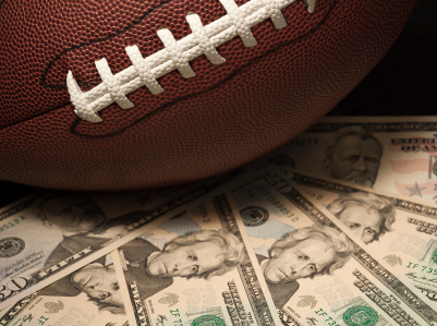 A football sitting on a fanned-out stack of 20 dollar bills.